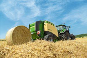 Deutz-Fahr Traktor mit Rundballenpresse von Krone bei der Strohernte am Feld.